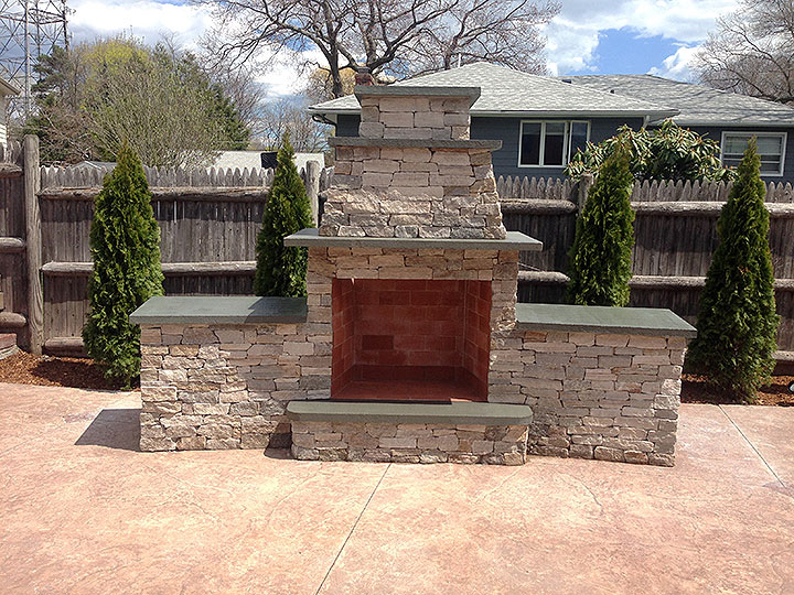 new england landscaper Andover, MA stone fireplace with wood storage and storage shelves (behind), plantings