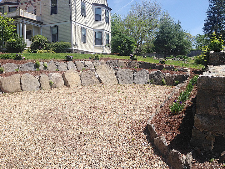 new england landscaper Andover, MA ornamental retaining boulders, planting beds, plantings, pea stone driveway