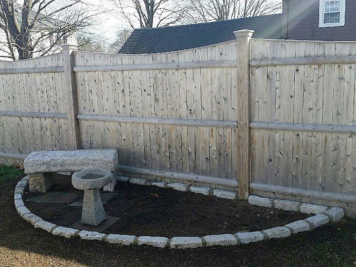 new england landscaper Andover, MA curved cobblestone edge, granite bench, granite birdbath