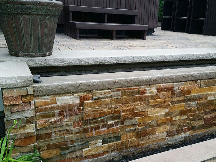 new england landscaper Andover, MA patio with water feature, natural stone veneer with limestone cap waterfall