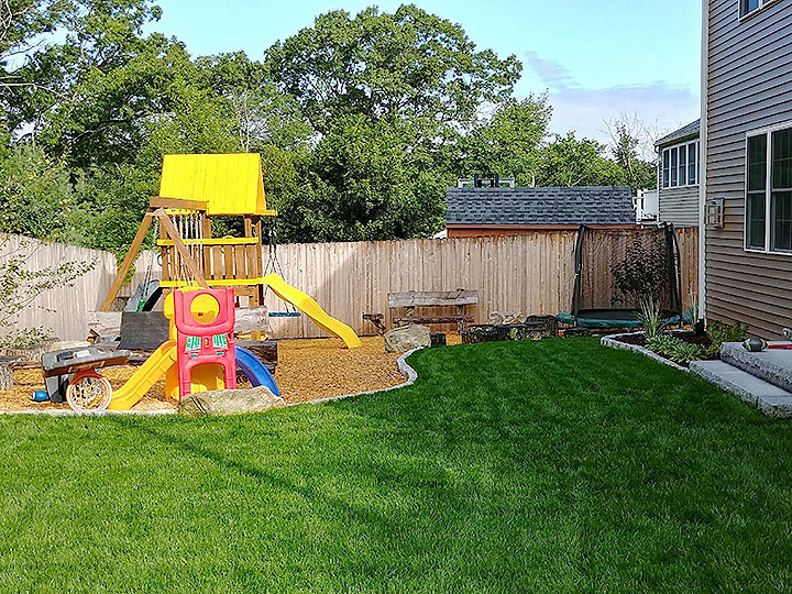 new england landscaper Andover, MA pea stone play area, curved cobblestone edge, granite steps, drywell, irrigation, plantings, hydroseed
