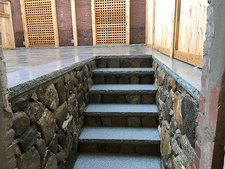 new england landscaper Andover, MA paver patio, natural stone risers, granite treads, natural stone wall with granite cap,  cedar growing trellis