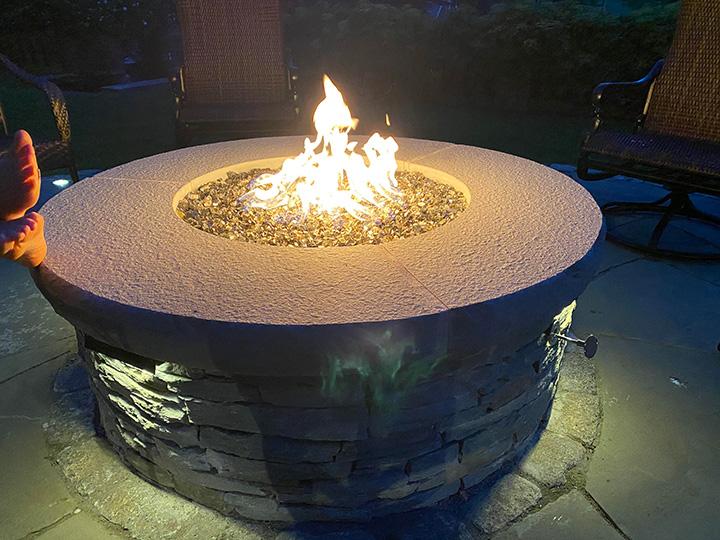 new england landscaper Winchester, MA stone fire pit with bluestone cap, recessed lighting, and cobblestone border