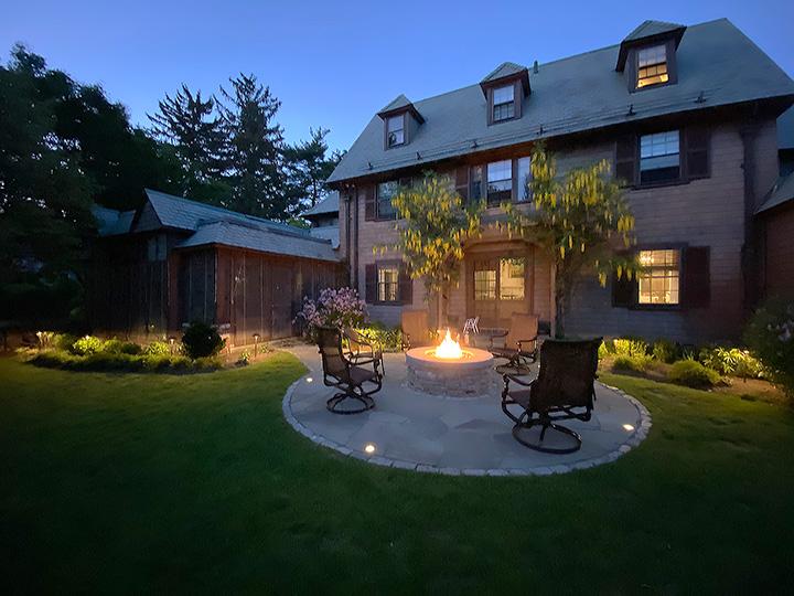 new england landscaper Winchester, MA stone fire pit with bluestone cap, recessed lighting, bluestone patio with cobblestone border
