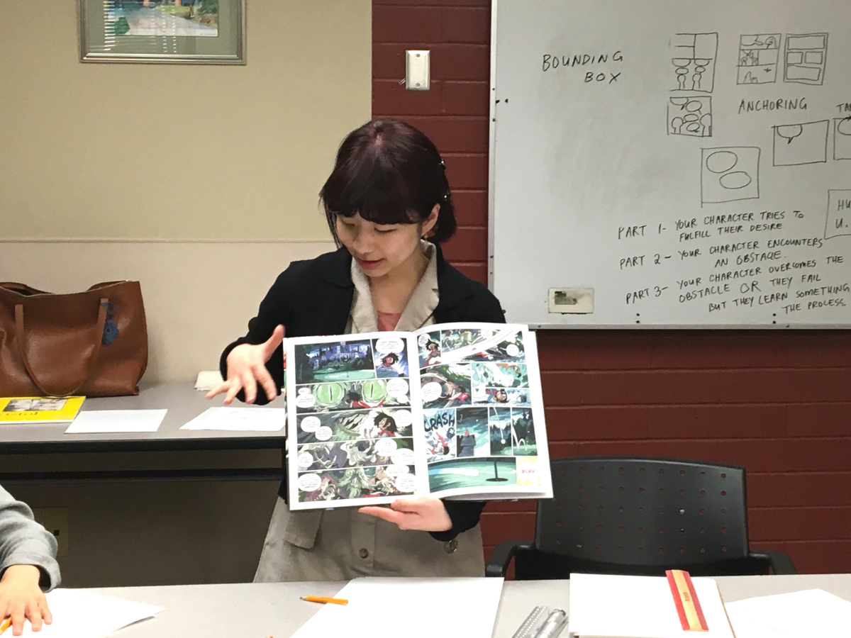 Janice Liu stands at the front of a whiteboard and points at a comic panel.