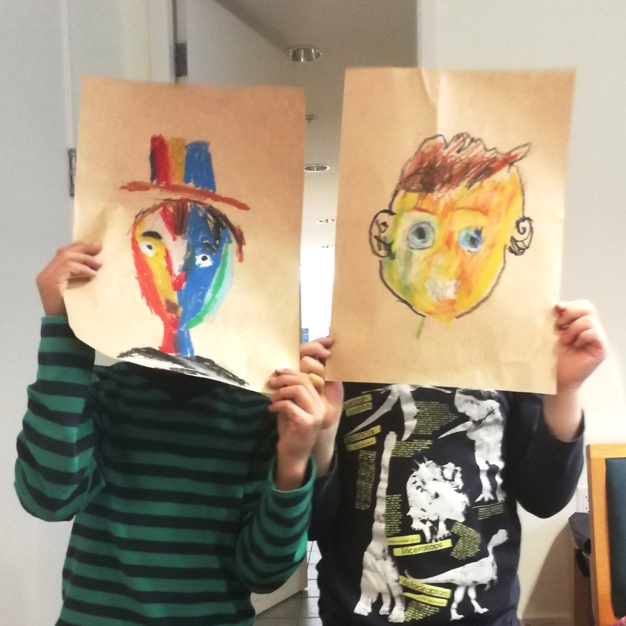 Two young children hold up their self portraits, drawn in oil pastel, over their faces.