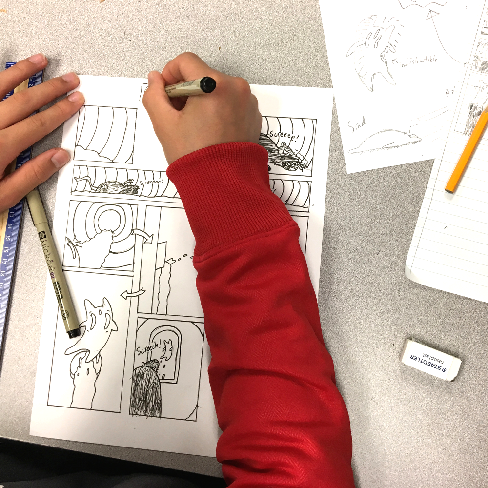 The hands of a student working on an inked comic page.