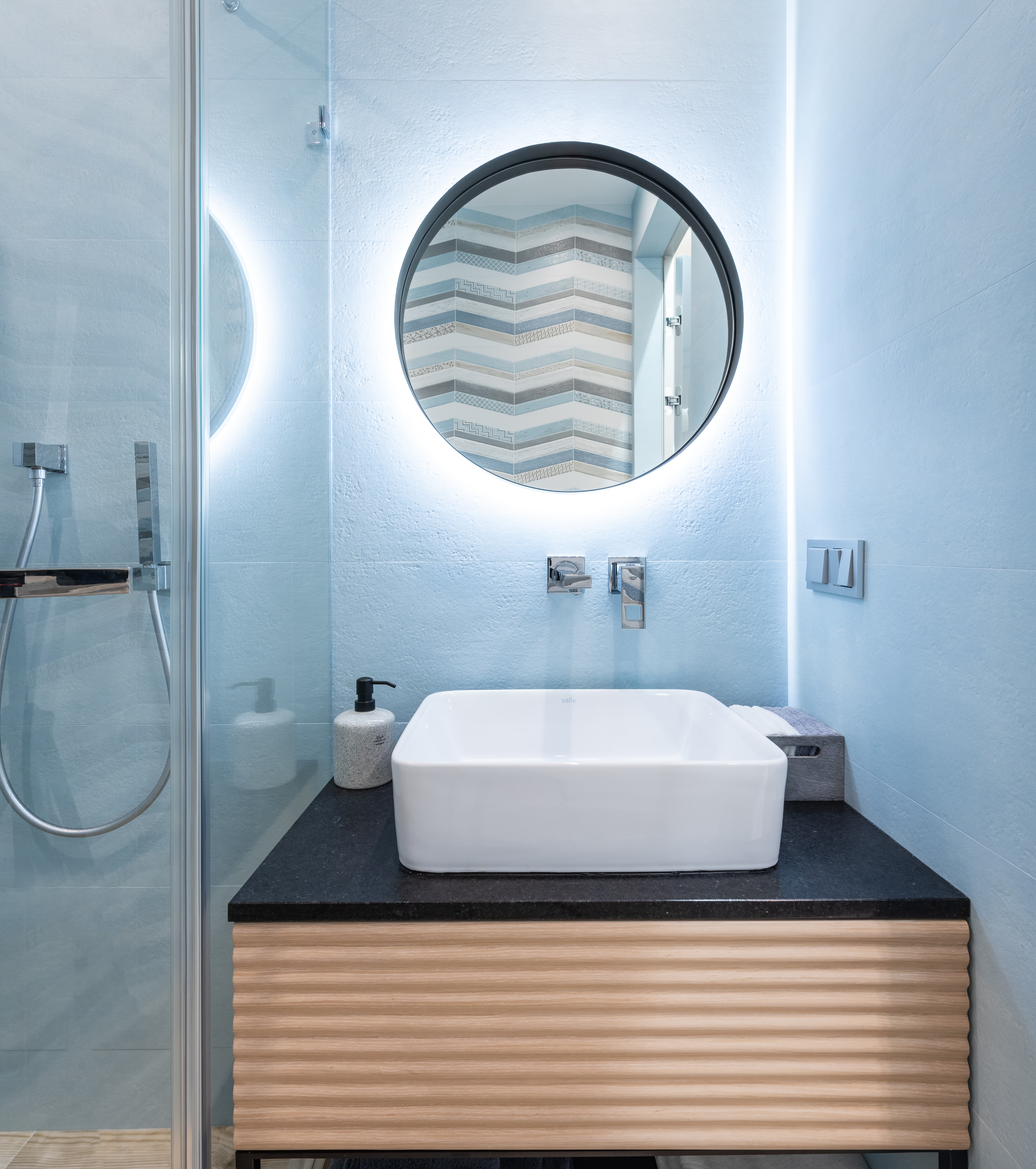 Photo of a bathroom sink and mirror above. The mirror has bright recessed light that brightens up the room.