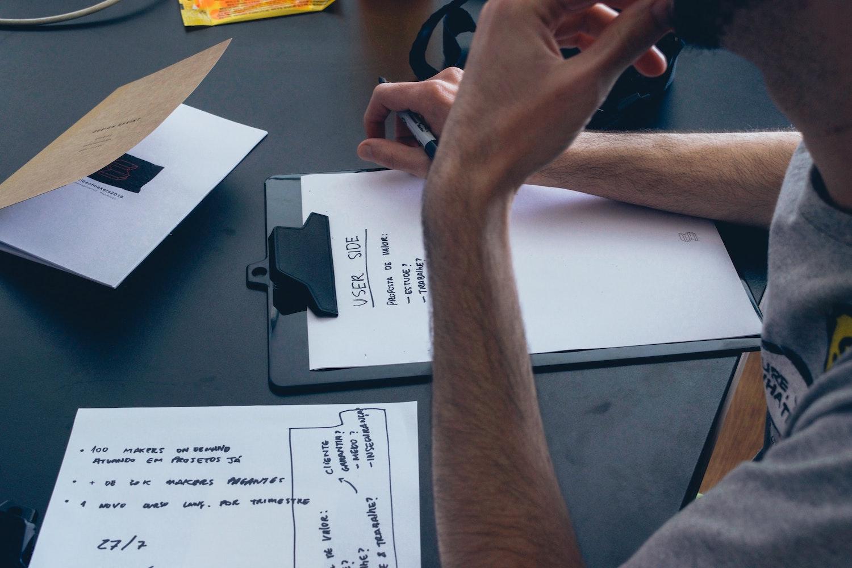 Mann schreibt auf Papier Brainstorming