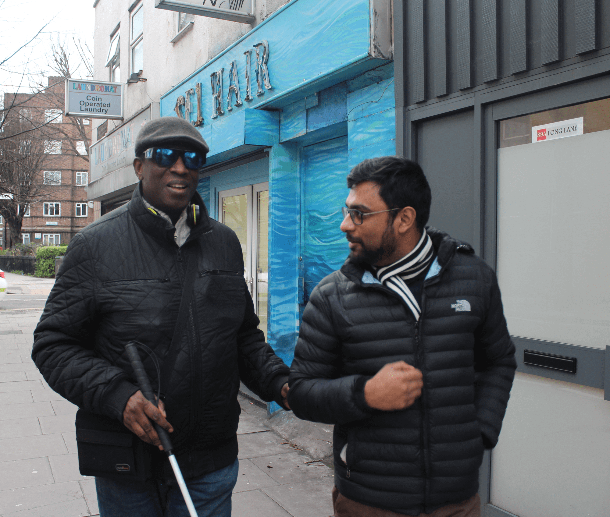Visually impaired man walking and talking with a volunteer
