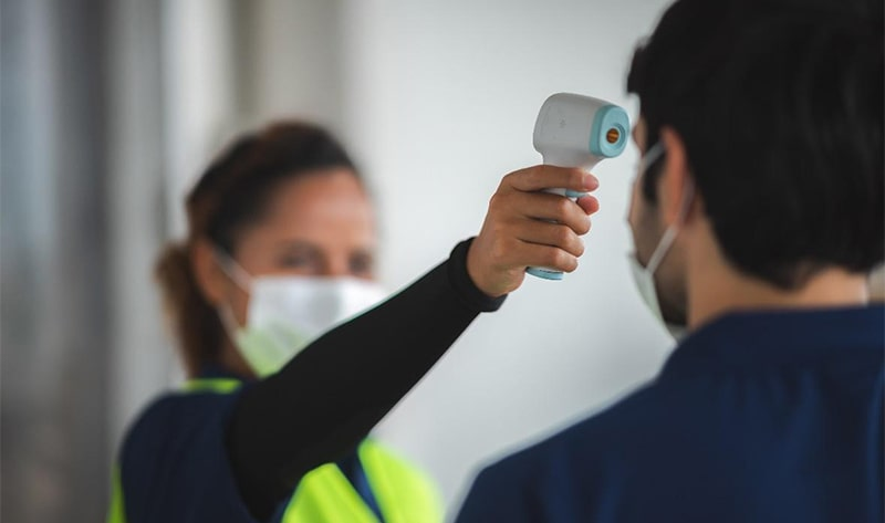 Person taking an employee's temperature with an infrared thermometer