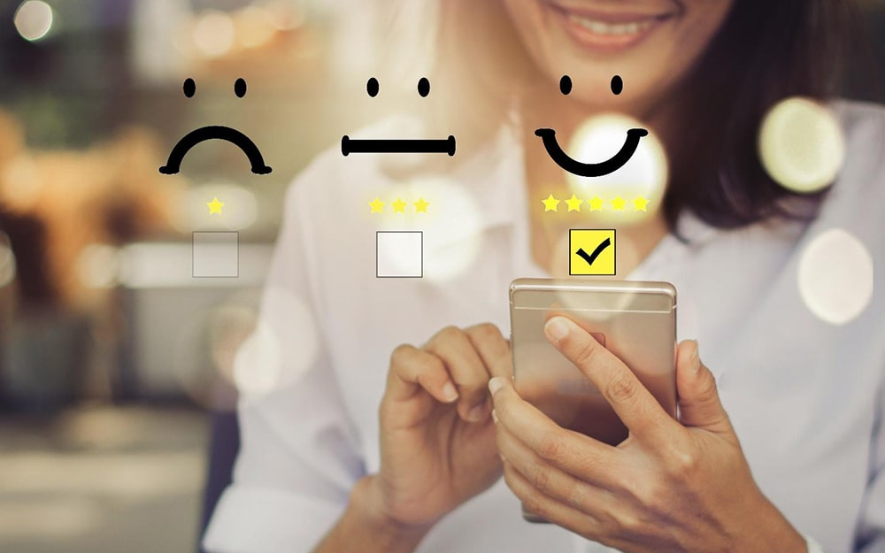 woman using phone with three emojis and checkboxes above: sad face emoji with one star, straight line emjoi with three stars, happy face emoji with five stars and a checked box.