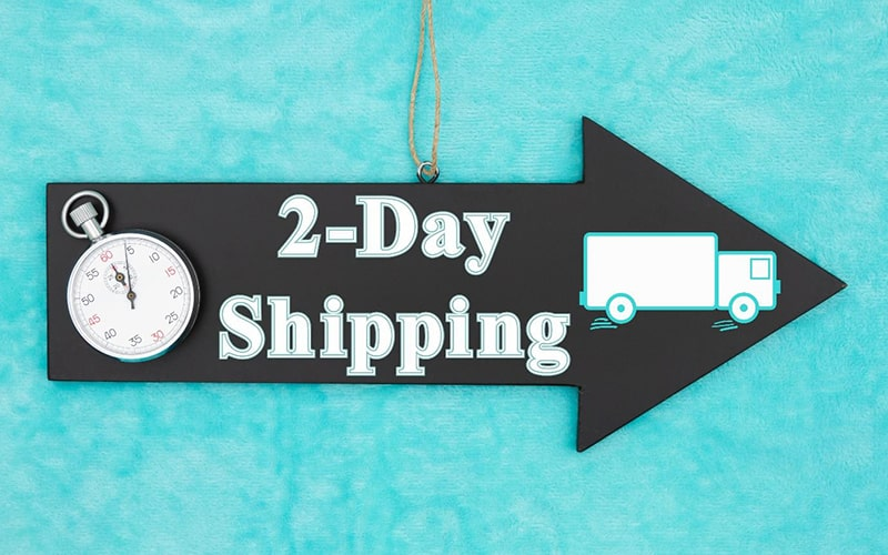 blue background with a black arrow pointing right. inside the arrow are a stopwatch, an illustration of a shipping truck, and the text '2-day shipping'