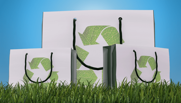 three paper shopping bags sitting on the grass. each bag is white and has a green recycling sign on it.