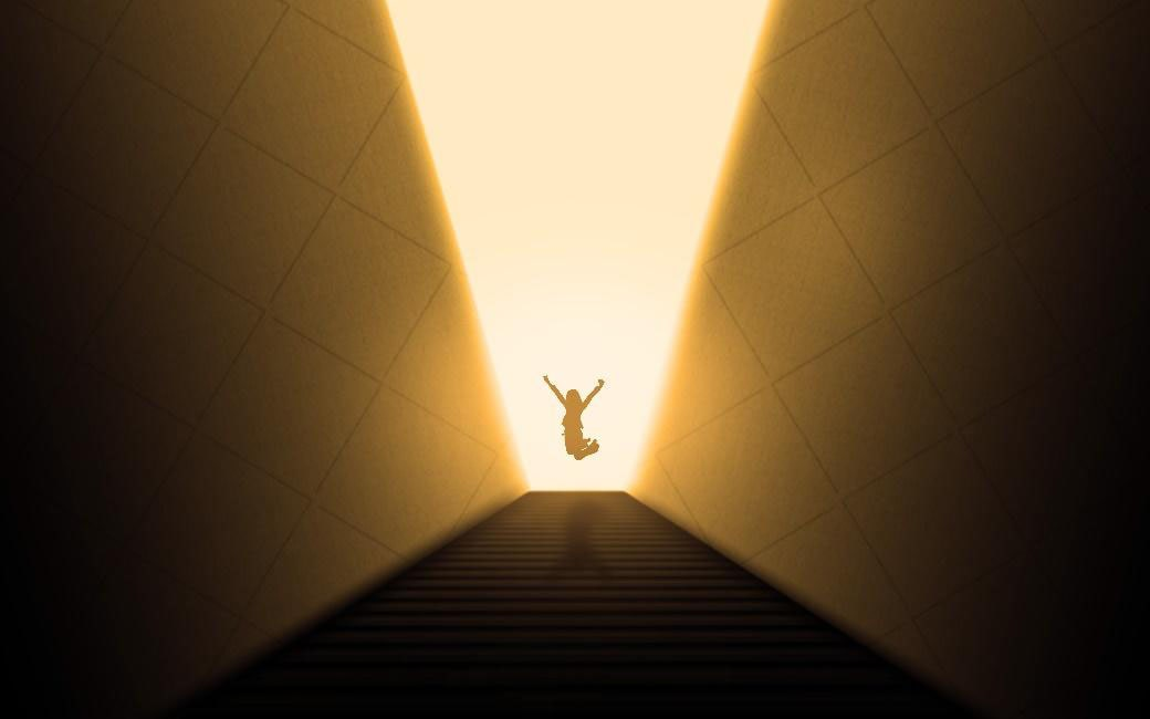 silhouette of a person at the top of a set of stairs, jumping with their arms outstretched above their head