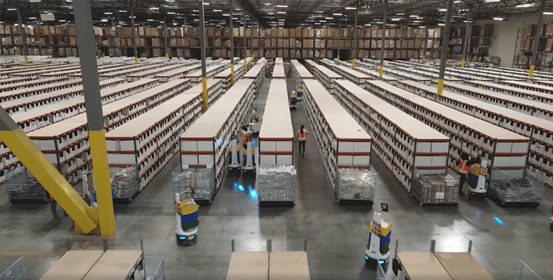 port logistics group warehouse from a high angle. storage lines the aisles and locusbots help fulfill orders.