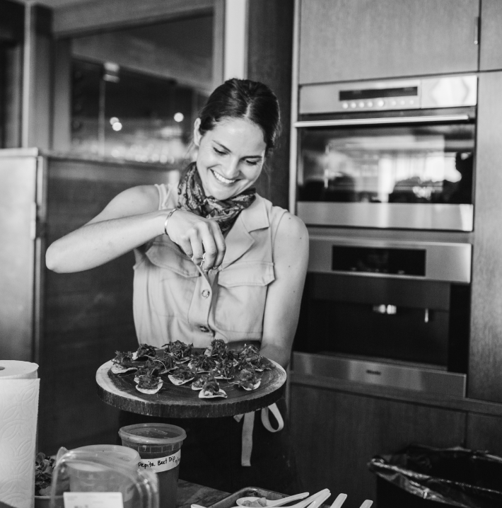 TULA Culinary Director Lauren stands in a kitchen holding a plate of snacks with her left hand an sprinkling toppings over the plate with her right hand. She is looking down at the plate and smiling.