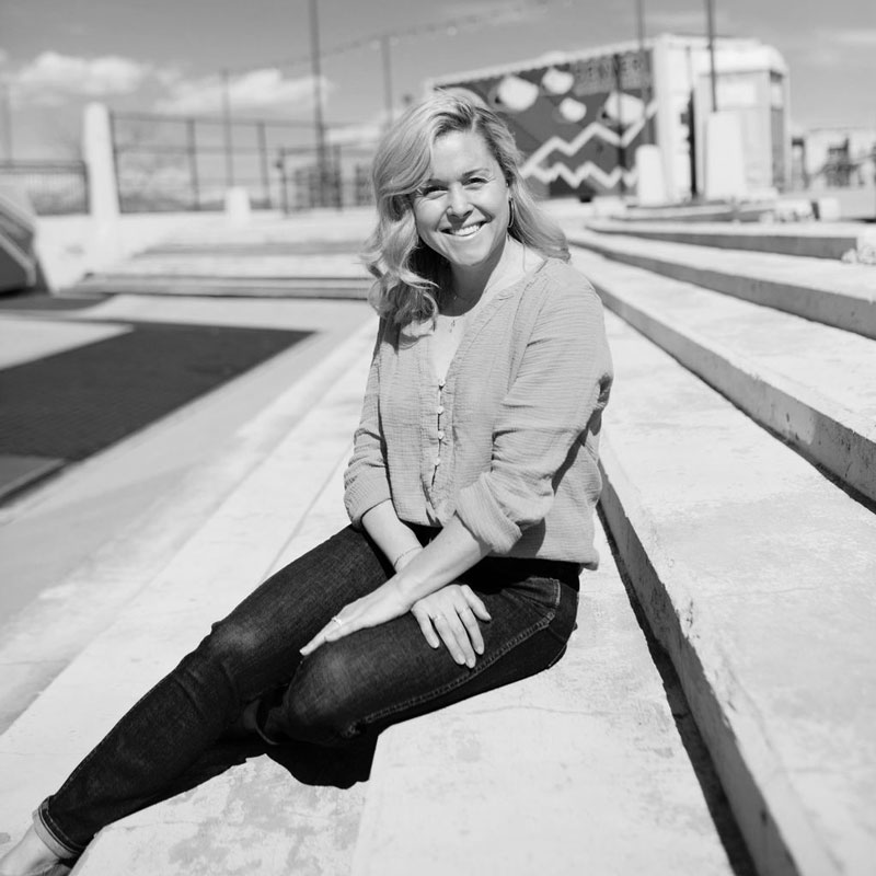 TULA wellness partner Edie Horstman smiles at the camera. She is seated outside on a series of concrete steps.