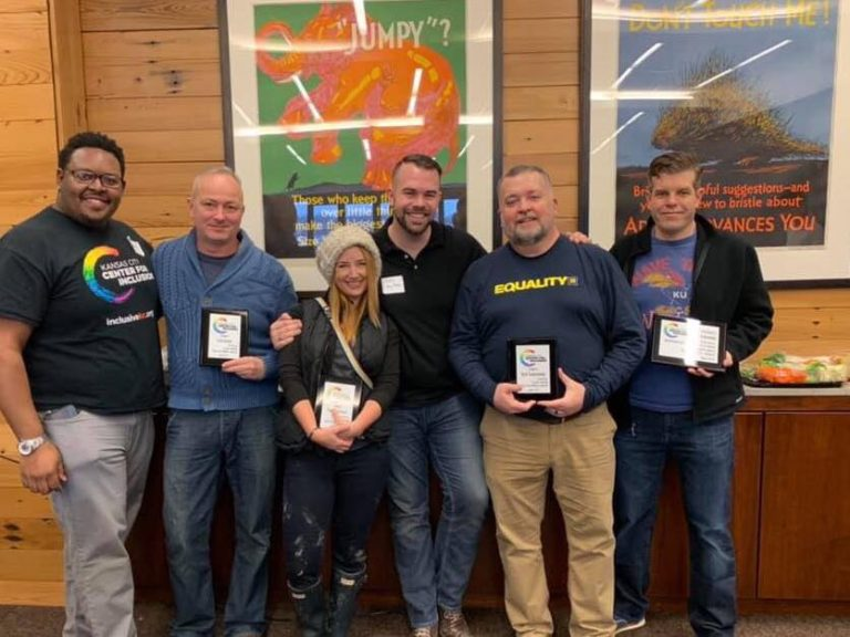 A group of volunteers standing together smiling holding thank you plaques