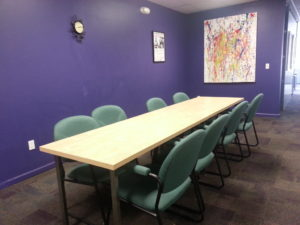 Image of a long wooden table with chairs on both sides in front of a purple wall with a painting hanging on the wall.