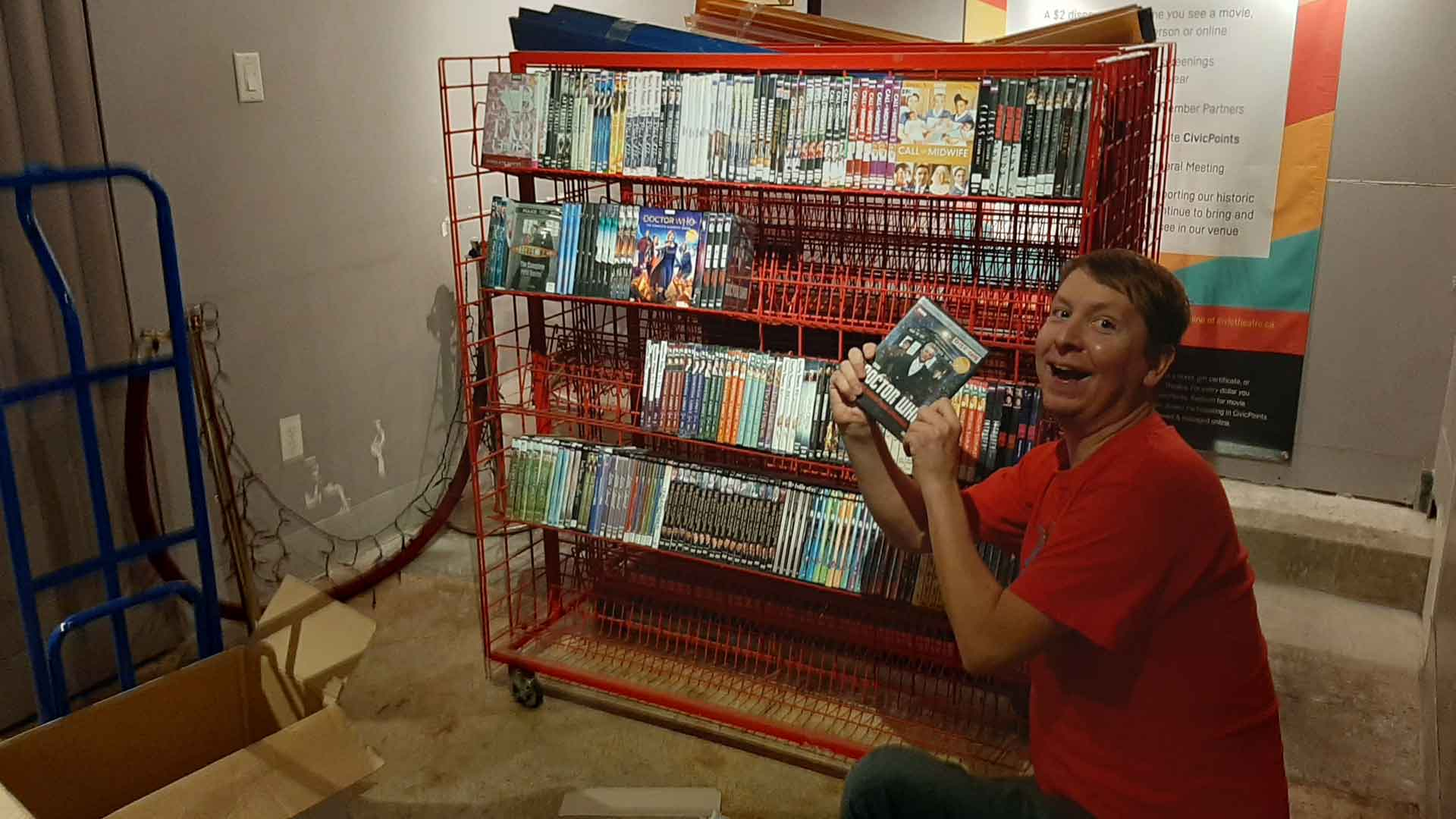 Reos Video - Cole holding DVDs in front of red shelves