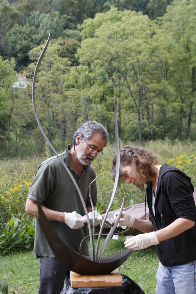 Kate Vogel and John Littleton working outdoors on a metal and glass sculpture.