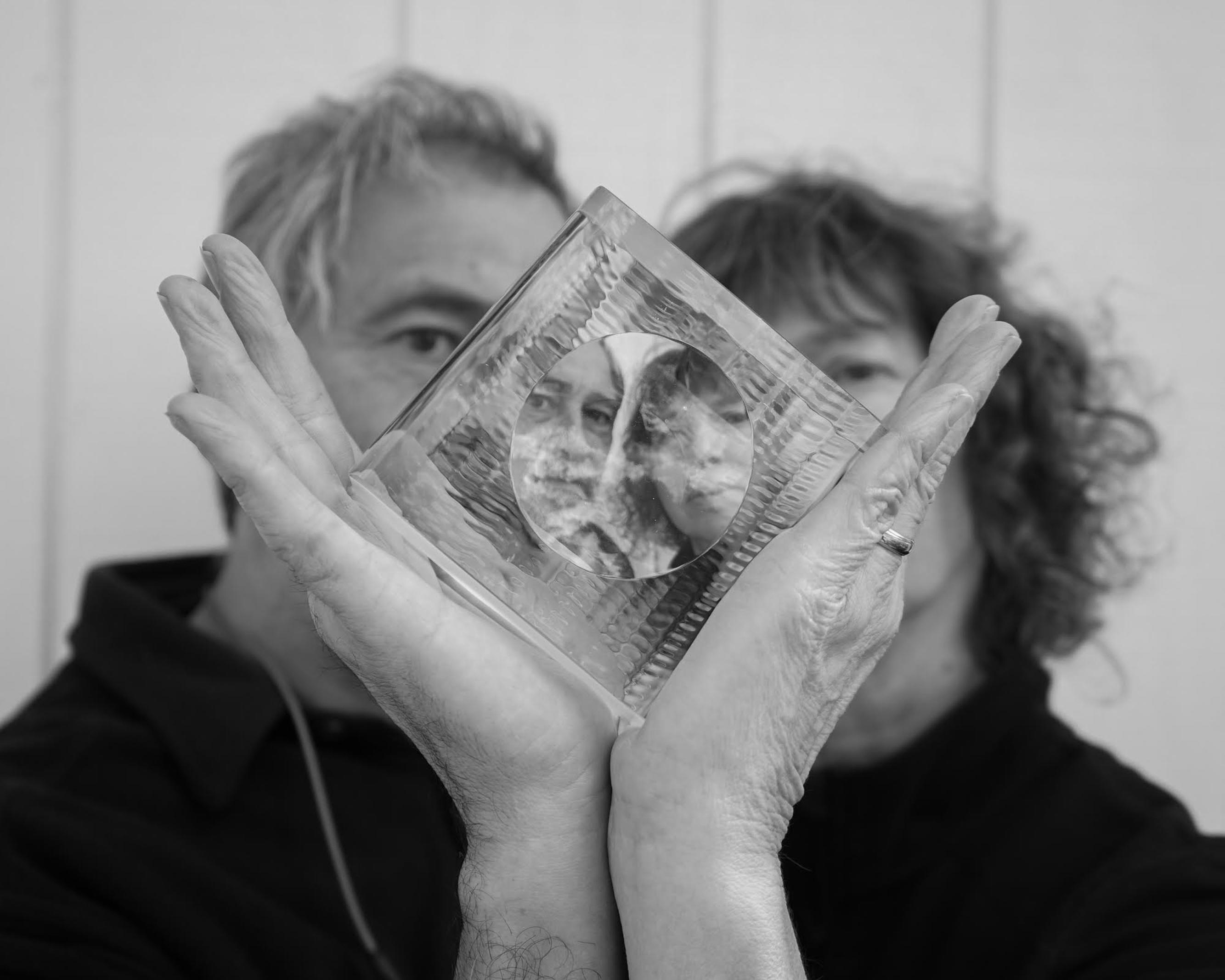 Kate Vogel and John Littleton seen through a glass cube.