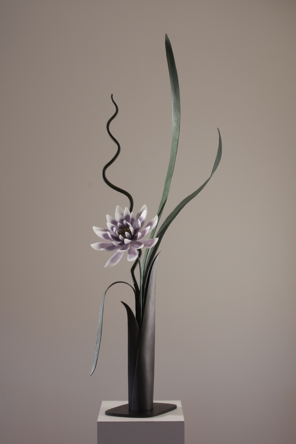 Sculptural flower arrangement in cast glass with white and lavender flower, green steel leaves, tall vase in deep brown.