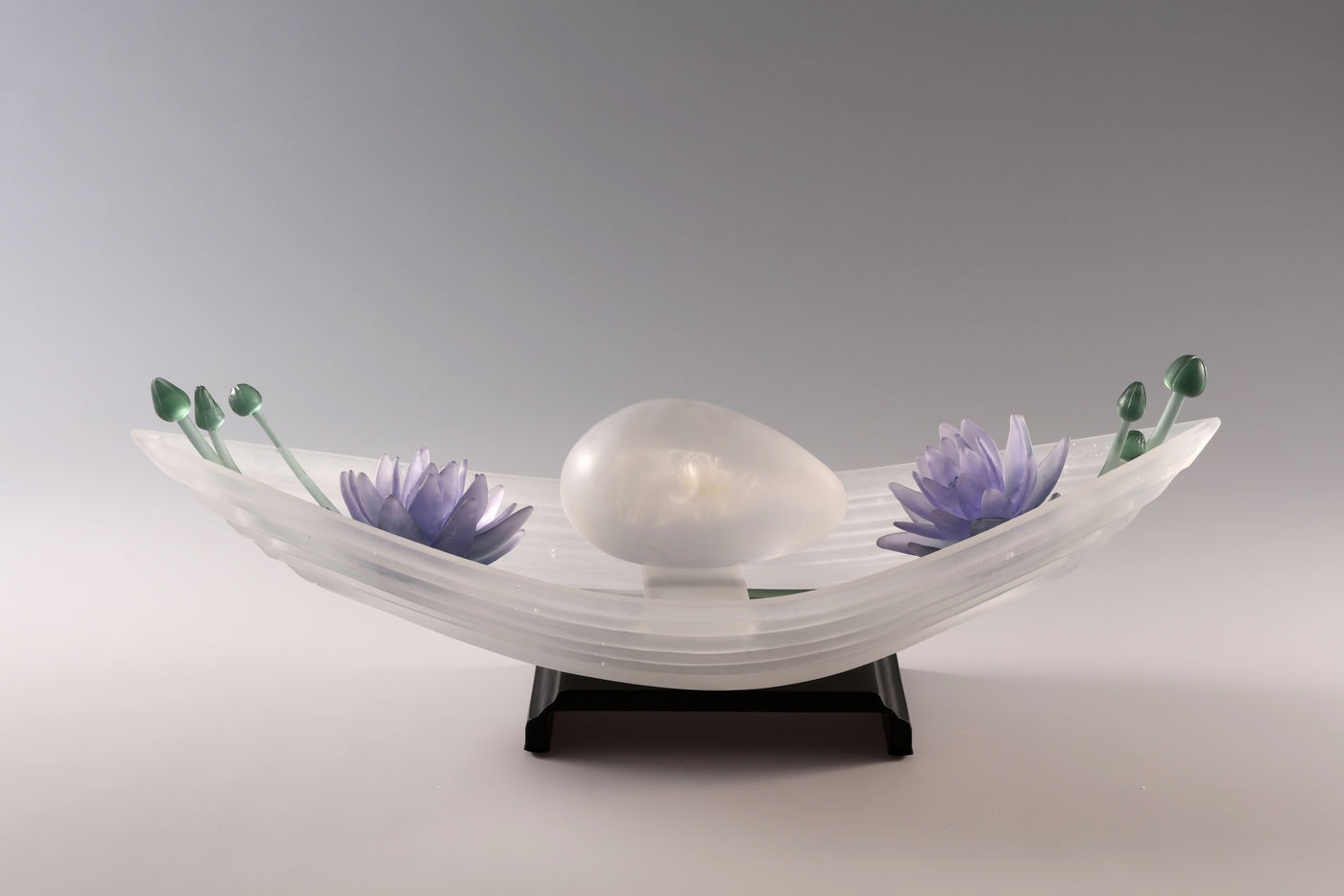 Sculpture of cast glass boat and lavender flowers with green buds on steel base.