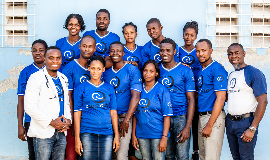The capracare team huddled together smiling and wearing their capracare shirts.