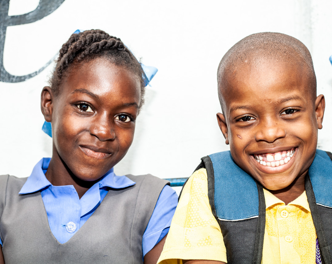 Two school children looking at the camera smiling.