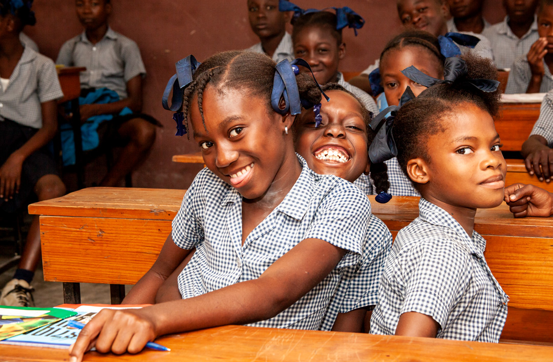 Three girls smiling and posing for the camera.