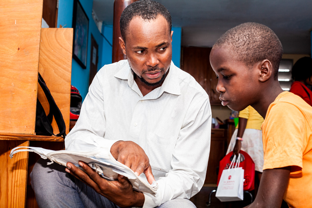 A capracare worker helping a student with his work.
