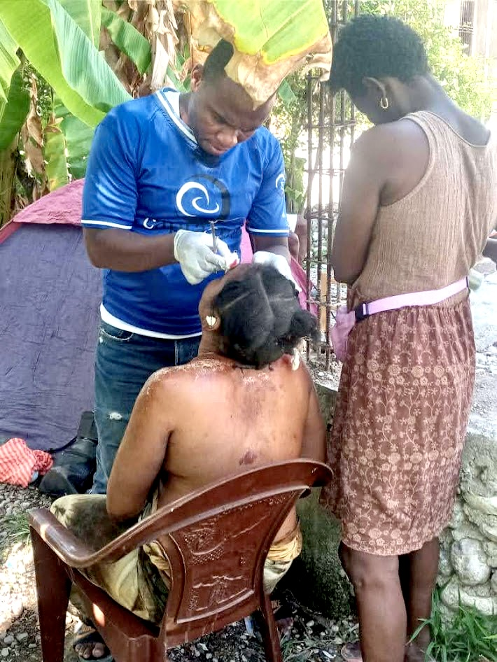 capracare's Dr. Smith helping a survivor of the earthquake