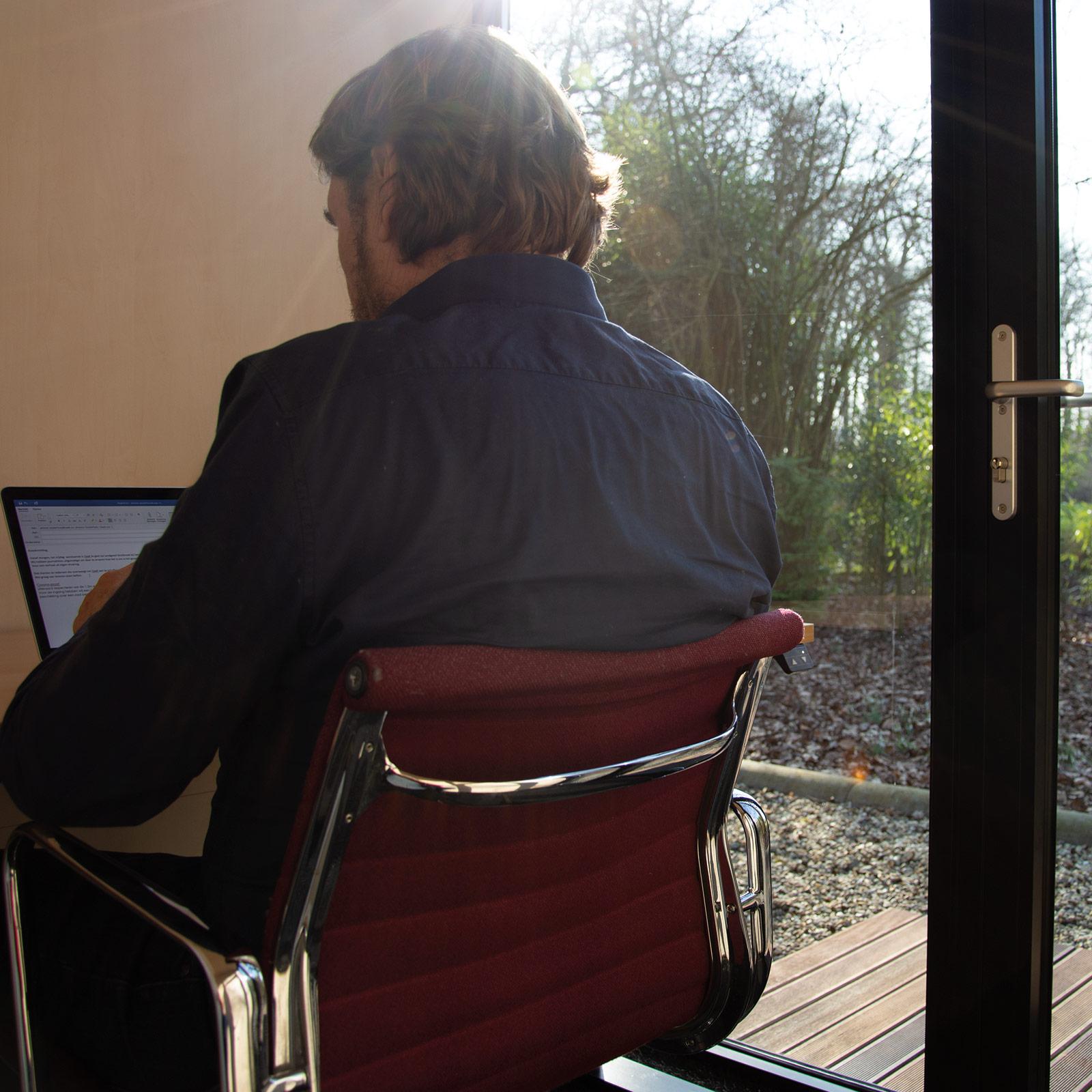 Man werkzaam binnen het tuinkantoor met uitzicht op het groen.