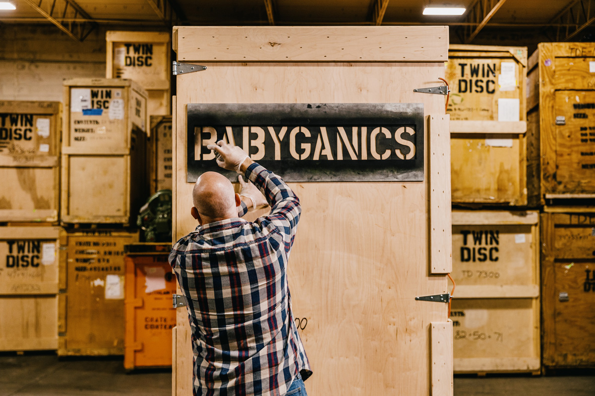 Abe stenciling Babyganics name on the exterior of a shipping crate.