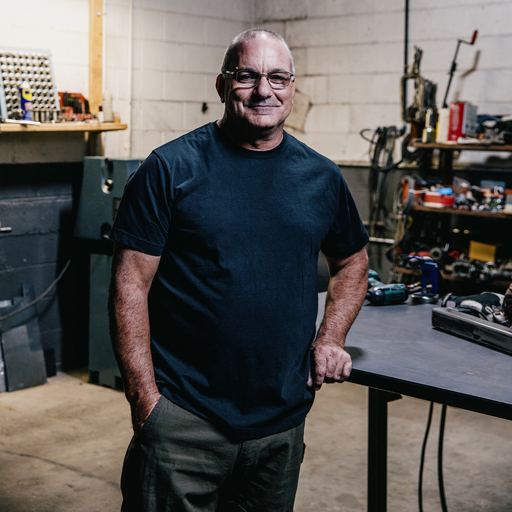 Portrait of Tom standing in his work space.