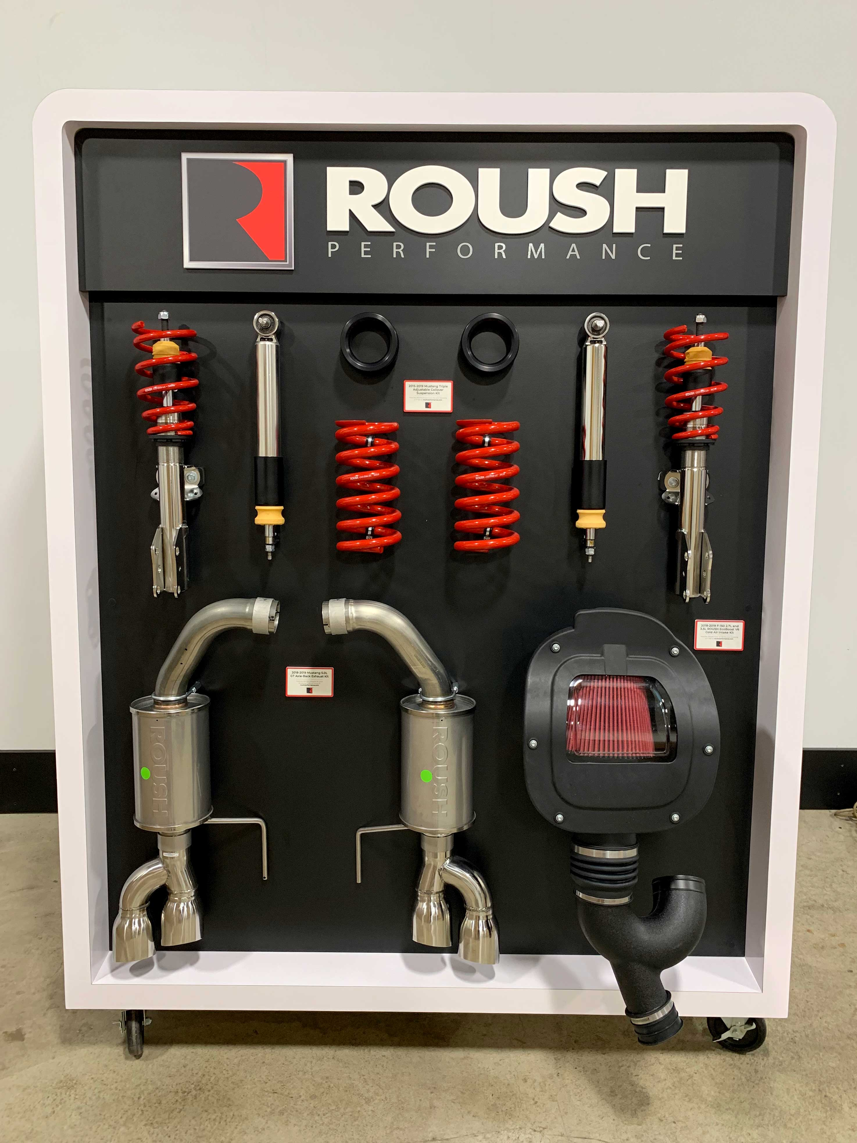 Rolling kiosk for Roush displaying a collection car part products like springs and exhaust pipes.