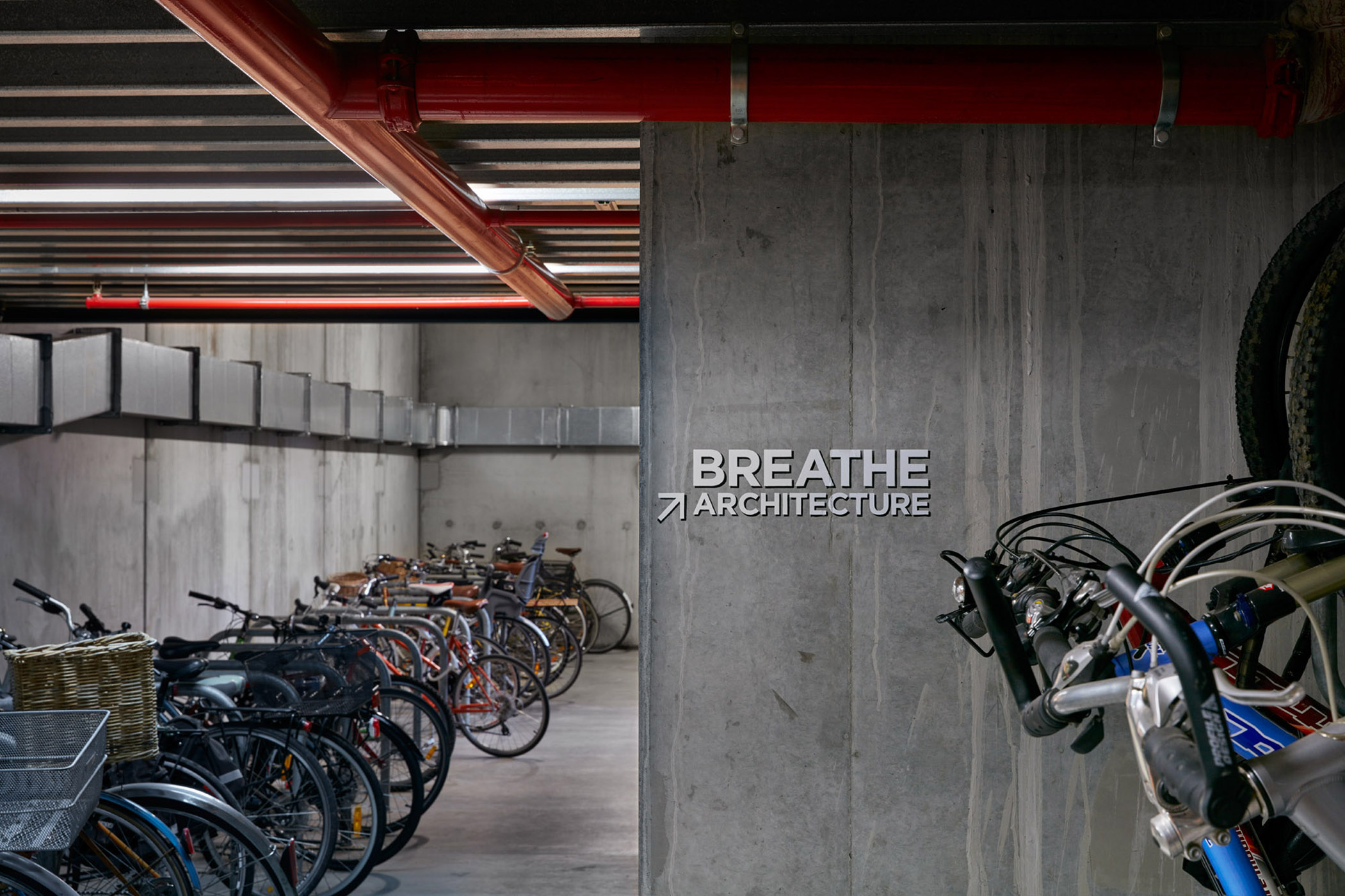 A large basement space with lots of bicycles parked next to each other. A handwritten sign reads Breathe Architecture.