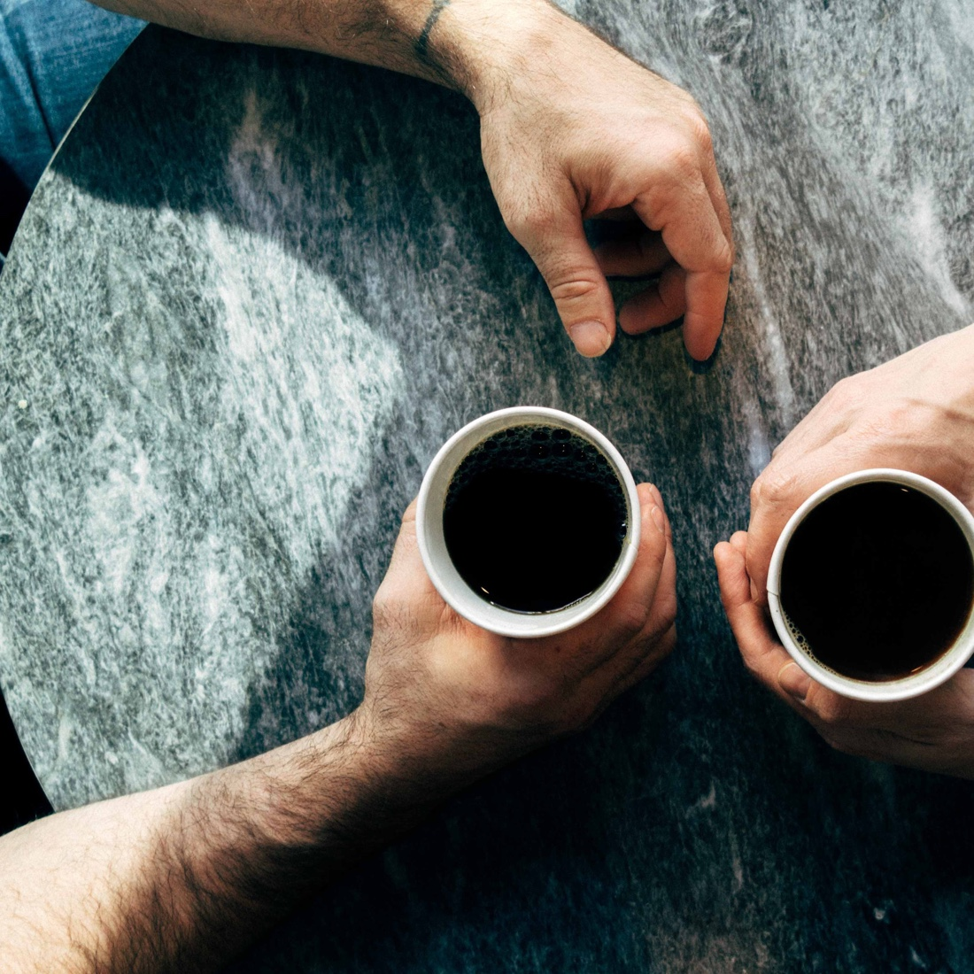 Birdseye view of two pairs of hands, each holding coffee cups, resting on a table.