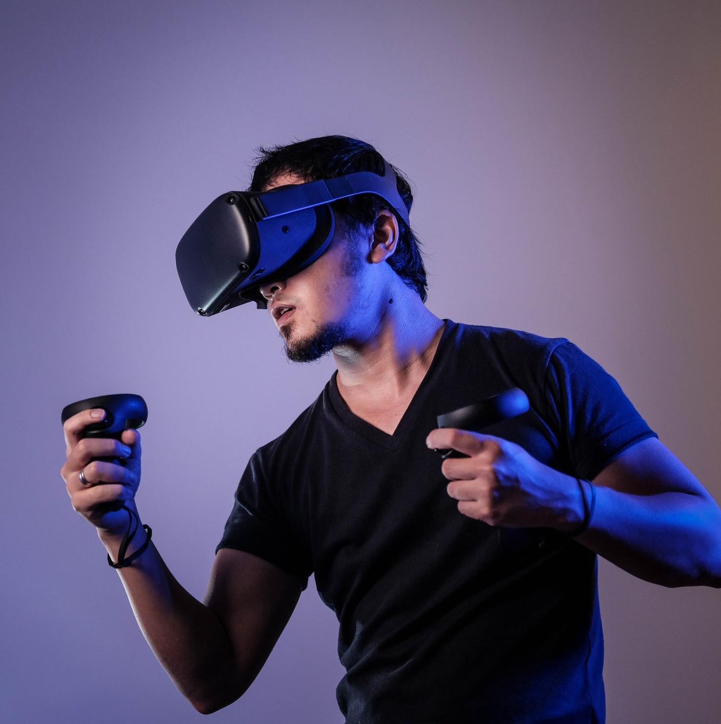 A photo of a man wearing a Virtual Reality headset playing a Virtual Reality game