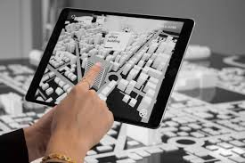 A photo of a city planner using Augmented Reality to visualize a city in 3D from a 2D map.
