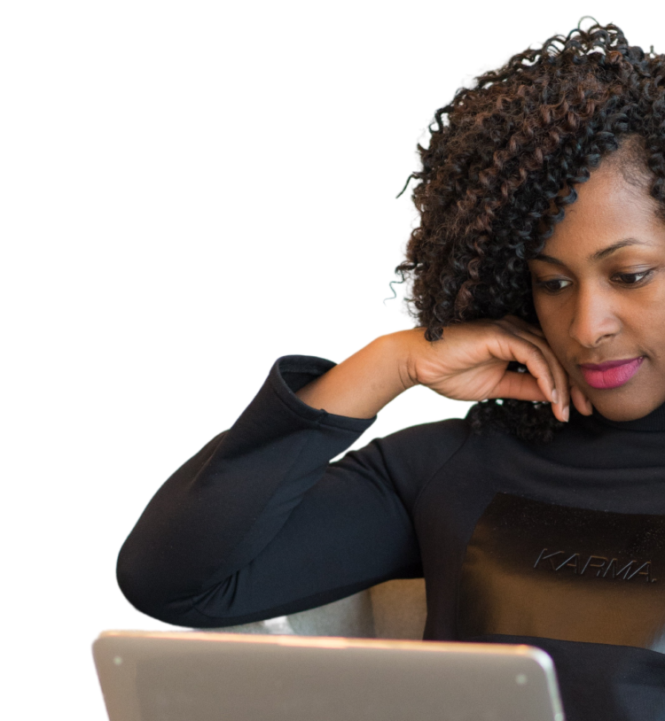 Young black woman with curly hair in a sweater and scarf looking down at laptop.