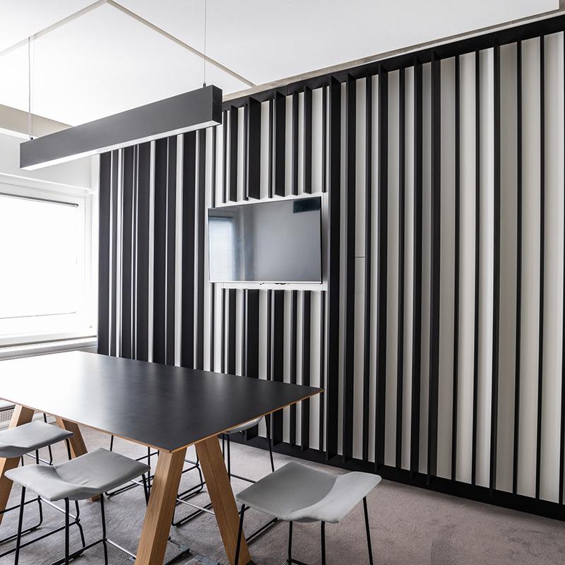 Die moderne und besondere Wandverkleidung erinnert mit ihren unterschiedlichen Streifen- und Lückenbreiten an einen Strichcode. Diese Wandvertäfelung stellt nicht nur einen thematischen Bezug zum Unternehmen her, sondern ist zudem noch ein echter Blickfang.