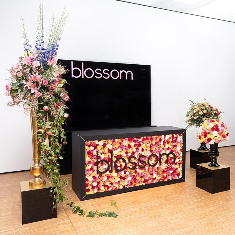 Dieser edle Messestand in mattem Schwarz zieht mit seiner farbenfrohen Blumenwand und den dazugehörigen Requisiten alle Besucherblicke auf sich.