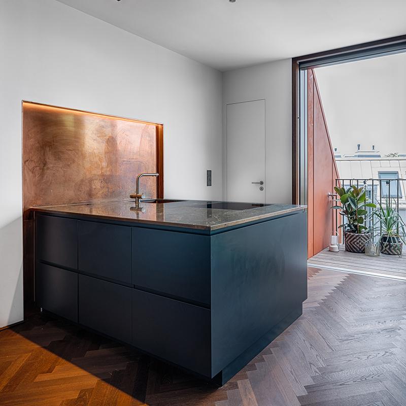Dieser schöne und schlichte Küchenblock mit einer Arbeitsplatte aus Marmor lässt Küchenträume wahr werden. Das Lichtelement aus Kupfer am Wandende bringt doppelte Wärme in den Raum. So sorgt die Küche selbst an grauen Tagen für ein gemütliches und sonniges Wohlgefühl.