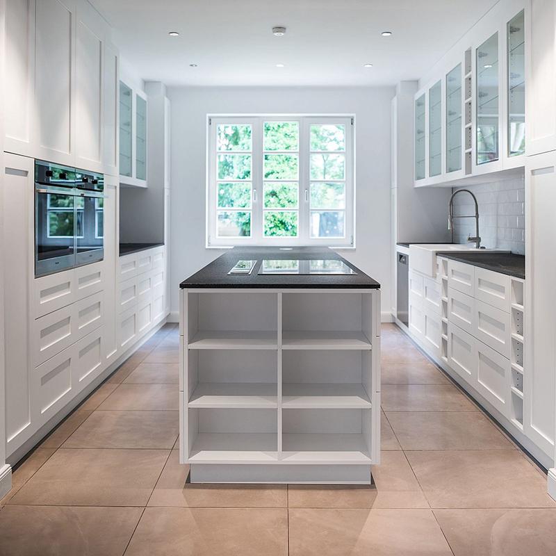 Diese helle und elegante Küche mit Kochinsel erstrahlt in einem schönen Weiß und lädt mit einer ausladenden Arbeitsplatte aus hochwertigem Granit zum gemeinsamen Kochen ein.