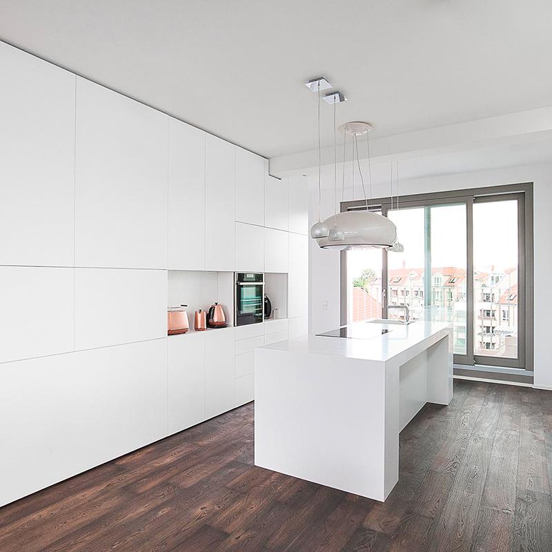Dieses minimalistische und luxuriöse Interieur verbindet Küche und Wohnzimmer mit einer bestehend aus Küchenzeile, Kücheninsel und einer Wohnzimmerschrankwand mit integrierter Badezimmertür bietet viele Funktionen in einem. Die Kücheninsel aus weißem Corian und matt-weiß lackierten Flächen lassen den Raum besonders hell und groß wirken. Hier lässt es sich ausgezeichnet wohnen und leben.