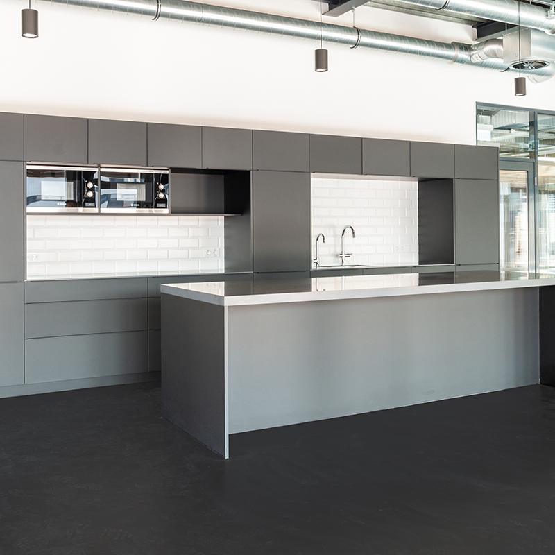 Diese edle Büroküche nimmt sich mit ihrem reduzierten Design zurück und besticht durch tolle Materialität. Einen besseren Ort für die ausgedehnte Mittagspause kann es fast nicht geben.