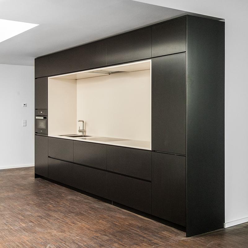 Das Design der edlen Einbauküche aus hochwertigem Corian in einem klassischen Schwarz-Weiß greift die dunklen Fensterrahmen innerhalb der Wohnung auf und es entsteht das Gefühl, ein weiteres großes Fenster erhelle den Raum.
